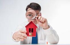 Uomo con una casa della carta e della lente d'ingrandimento Immagini Stock