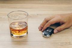 Uomo con una chiave a distanza dell'automobile e un vetro del whiskey di bourbon immagine stock