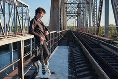 Uomo con una chitarra elettrica nel paesaggio industriale all'aperto Immagine Stock