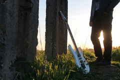 Uomo con una chitarra nel campo Immagine Stock