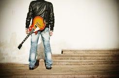 Uomo con una chitarra sulla sua spalla Immagini Stock