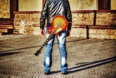 Uomo con una chitarra sulla sua spalla Immagine Stock