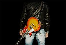 Uomo con una chitarra sulla sua spalla isolata su fondo nero immagini stock libere da diritti