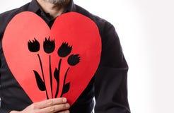 Uomo con una forma di carta rossa del cuore Fotografie Stock