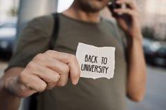 Uomo con una nota con il testo di nuovo all'università Fotografia Stock Libera da Diritti