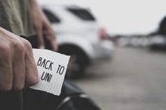 Uomo con una nota con il testo di nuovo all'università Fotografia Stock