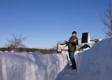Uomo con una pala della neve Fotografie Stock