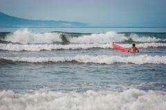 Uomo con una spuma rossa che nuota ad un'onda Spiaggia di Famara, Lanzarote, isole Canarie, Spagna Fotografia Stock Libera da Diritti