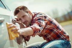 Uomo con una strofinata del microfiber la lucidatura dell'automobile Immagine Stock
