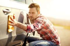 Uomo con una strofinata del microfiber la lucidatura dell'automobile Fotografia Stock