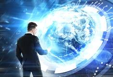 Uomo con uno smartphone, ologramma della terra Fotografia Stock