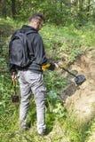 Uomo con uno zaino sul suo supporti posteriori nella foresta con un metal detector nella sue mano e ricerche l'area alla ricerca  immagine stock