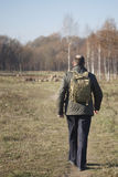 Uomo con uno zaino sulle sue spalle che cammina sul percorso in parco Fotografia Stock Libera da Diritti