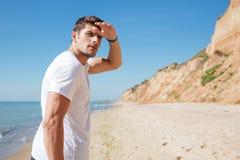 Uomo concentrato che cammina sulla spiaggia e che guarda lontano Immagine Stock