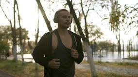 Uomo concentrato che corre e che ascolta la musica favorita tramite le cuffie Pareggiare di mattina il parco di verde nel nero archivi video