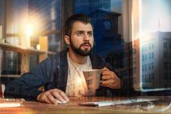 Uomo concentrato che fissa allo schermo mentre bevendo tè Fotografia Stock