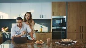 Uomo concentrato che lavora alla cucina di lusso Moglie sorridente che parla con il marito archivi video