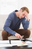 Uomo concentrato che per mezzo del calcolatore che conta le sue fatture Immagine Stock