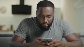 Uomo concentrato che si siede con il telefono Ritratto del messaggio di battitura a macchina dell'uomo di colore archivi video