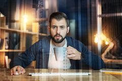 Uomo concentrato che tiene una tazza e che esamina il suo monitor Fotografia Stock Libera da Diritti