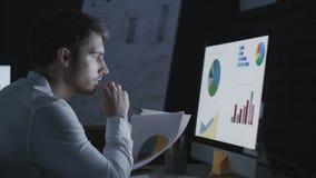 Uomo concentrato di affari che analizza documento finanziario nell'ufficio di notte video d archivio