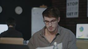 Uomo concentrato di affari che lavora con la carta del documento vicino al computer portatile in ufficio scuro video d archivio