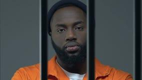 Uomo condannato afroamericano pericoloso che esamina macchina fotografica attraverso le barre della prigione archivi video