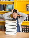 Uomo confuso che esamina i libri impilati in biblioteca Fotografia Stock