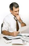 Uomo confuso che legge un'istruzione della Banca o del Bill Fotografie Stock
