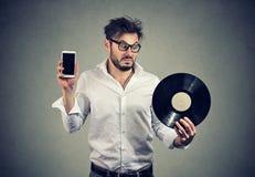 Uomo confuso con vinile e lo smartphone Fotografie Stock