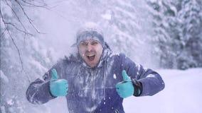 Uomo congelato allegro nell'inverno, neve di caduta, pollice su archivi video