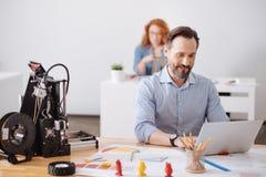 Uomo contentissimo allegro che elabora una nuova progettazione Immagini Stock