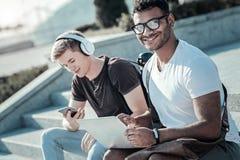 Uomo contentissimo felice che si siede con un computer portatile Immagini Stock