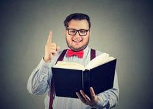 Uomo contento che ha idea mentre libro di lettura Fotografia Stock