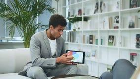 Uomo convenzionale nero che fa presentazione con la compressa Giovane uomo afroamericano in vestito che si siede nell'ufficio sul
