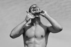 Uomo coperto di schiuma che si rade con il rasoio e gridare fotografia stock