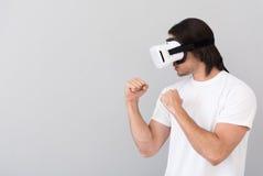 Uomo coraggioso che per mezzo del dispositivo di realtà virtuale fotografia stock libera da diritti