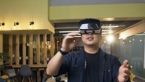 Uomo coreano di affari che lavora facendo uso dei vetri di realtà virtuale VR sui precedenti moderni dell'ufficio stock footage