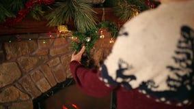 Uomo in corona d'attaccatura kniited di Natale del maglione sopra il camino autentico di pietra decorato con la ghirlanda infiamm archivi video