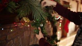 Uomo in corona d'attaccatura kniited di Natale del maglione sopra il camino autentico di pietra decorato con la ghirlanda infiamm video d archivio