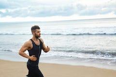 Uomo corrente che pareggia alla spiaggia durante l'allenamento di forma fisica all'aperto Spo Fotografia Stock