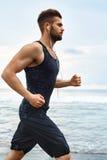 Uomo corrente che pareggia alla spiaggia durante l'allenamento di forma fisica all'aperto sport Fotografia Stock