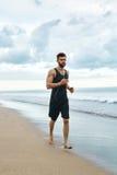 Uomo corrente che pareggia alla spiaggia durante l'allenamento di forma fisica all'aperto sport Fotografia Stock Libera da Diritti