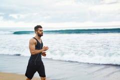 Uomo corrente che pareggia alla spiaggia durante l'allenamento di forma fisica all'aperto sport Fotografie Stock