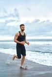 Uomo corrente che pareggia alla spiaggia durante l'allenamento di forma fisica all'aperto sport Fotografie Stock Libere da Diritti