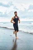 Uomo corrente che pareggia alla spiaggia durante l'allenamento di forma fisica all'aperto sport Immagini Stock Libere da Diritti