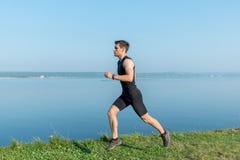 Uomo corrente dell'atleta che pareggia sulla spiaggia Allenamento di mattina di estate Fotografia Stock