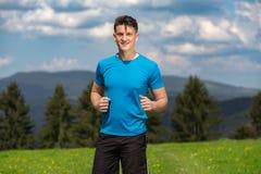 Uomo corrente di forma fisica che sprinting all'aperto nel bello paesaggio fotografia stock