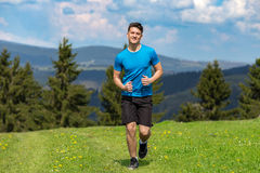 Uomo corrente di forma fisica che sprinting all'aperto nel bello paesaggio fotografie stock libere da diritti