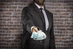 Uomo corrotto che tiene le fatture di soldi immagine stock